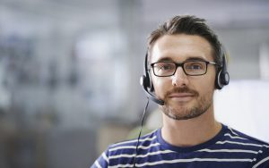 Portrait of a handsome young businessman wearing a headset in the office